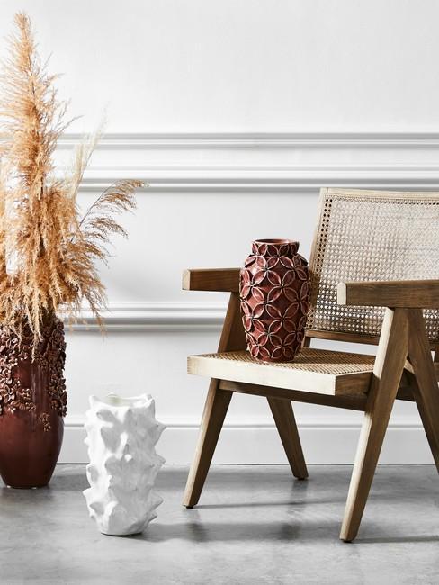 Barok stijl header witte wand met ornamenten met vazen en rotan stoel