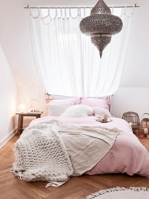 Zachte plaid van alpaca wol op roze bedlinnen in witte slaapkamer