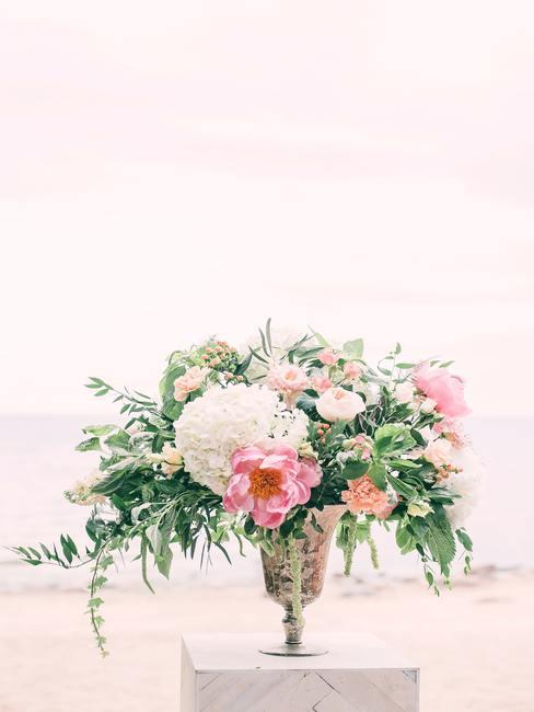 Een boeket van kunstbloemen in een decoratieve vaas op tafel als een boho-stijl bruiloft decoratie