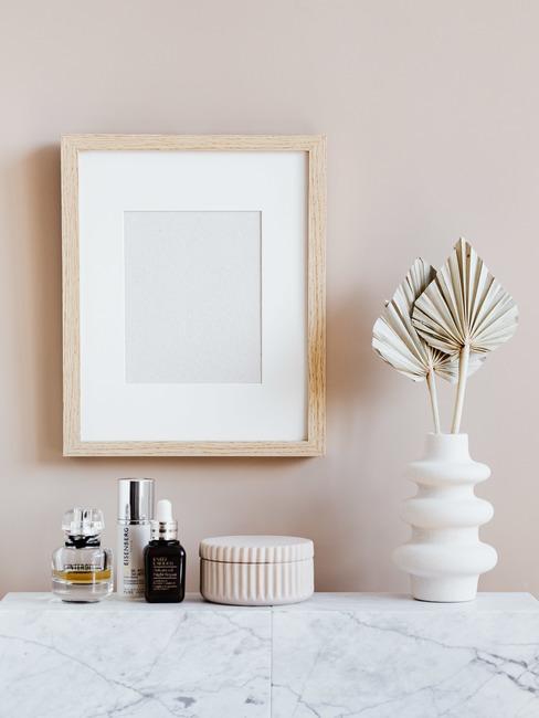 Shabby chic: fotolijstje op muur, witte dressoir met opbergdoos en witte vaas met decoratief object