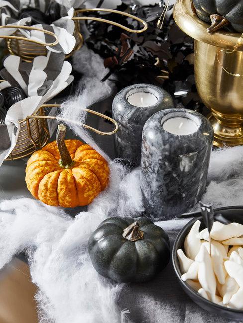 Halloween decoratie op houten tafel met zwarte kaarsenhouders en een pompoen