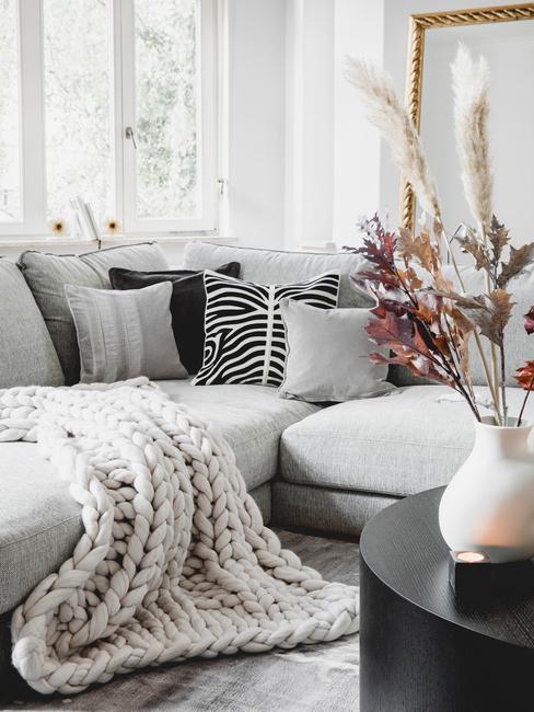 Een woonkamer in boho stijl met grijze zitbank met sierkussens en zwarte salontafel