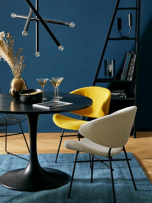 Corduroy fauteuils op blauw vloerkleed naast een zwarte eettafel