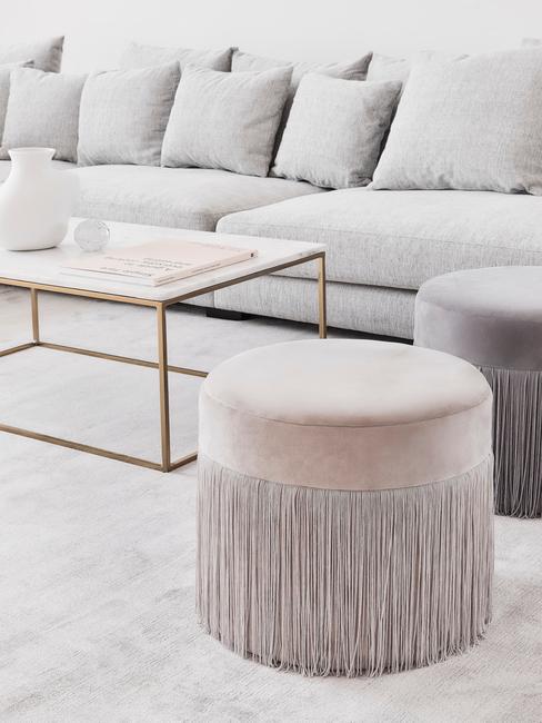Fluwelen poef met franjes naast een marmeren salontafel op de achtergrond van lichtgrijze zitbank