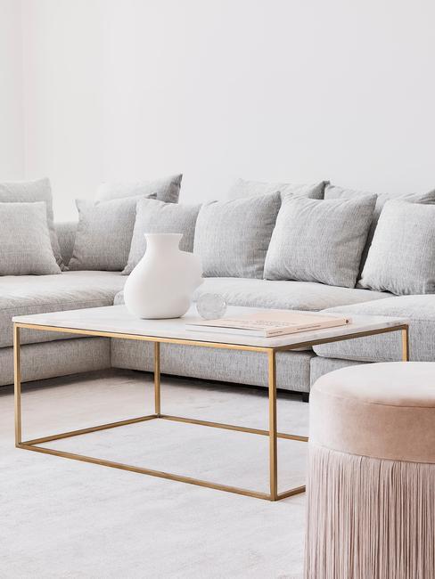 Goudkleurige salontafal op wit vloerkleed naast grijze zitbank met kussens en lichtroze poef met franjes