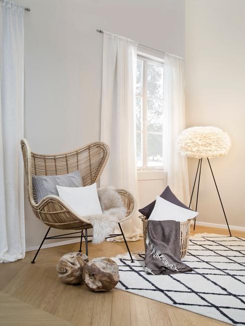 Rotan fauteuil met grijze en witte sierkussens op wit vloekleed en vloerlamp
