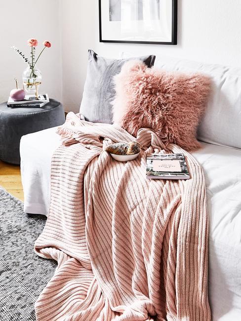 Schapenvacht kussens met zachte perzik plaid op witte zitbank