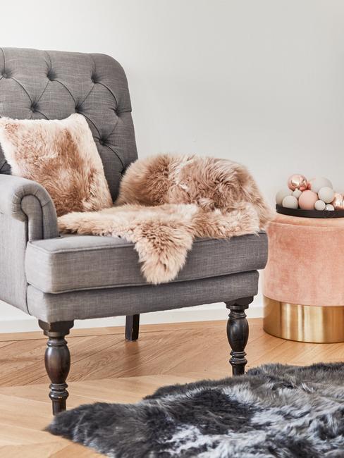 Grijze fauteuil met perzik sierkussen en plaid naast een fluwelen kruk
