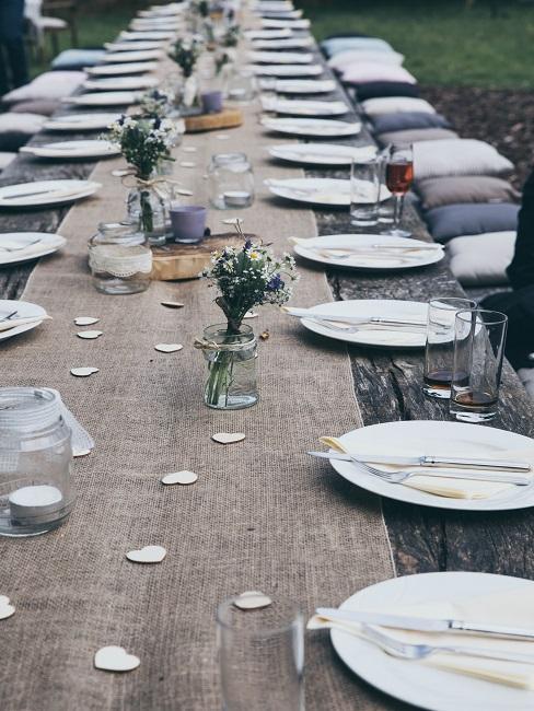 Gedekte tafel met borden en boeket bloemen