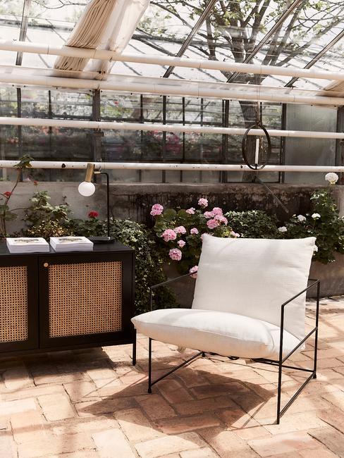 koloniaal interieur in kas met beige loungestoel