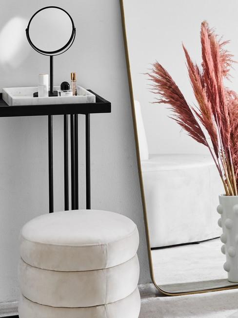 Witte poef en vaas voor staande spiegel tegen muur en sitetable