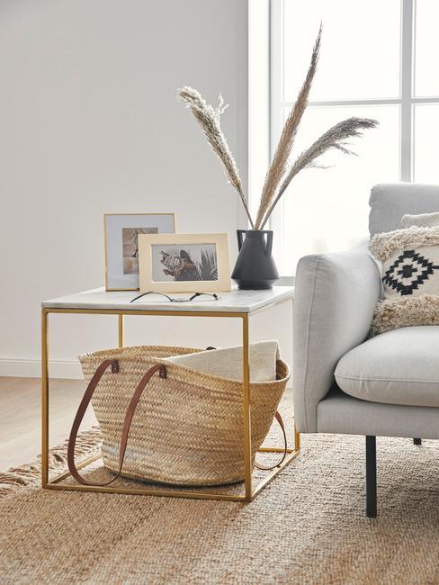 Bamboe trend: houten bijzettafel met vaas met bloemen en fotolijstje naast een grijze bank