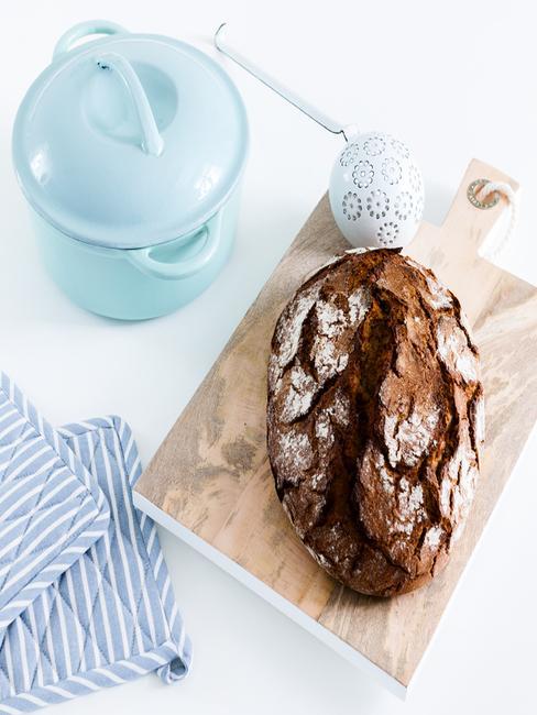 brood op houten plank met blauwe pot
