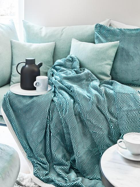 blauwe deken en blauwe kussens, witte bekers op de bank