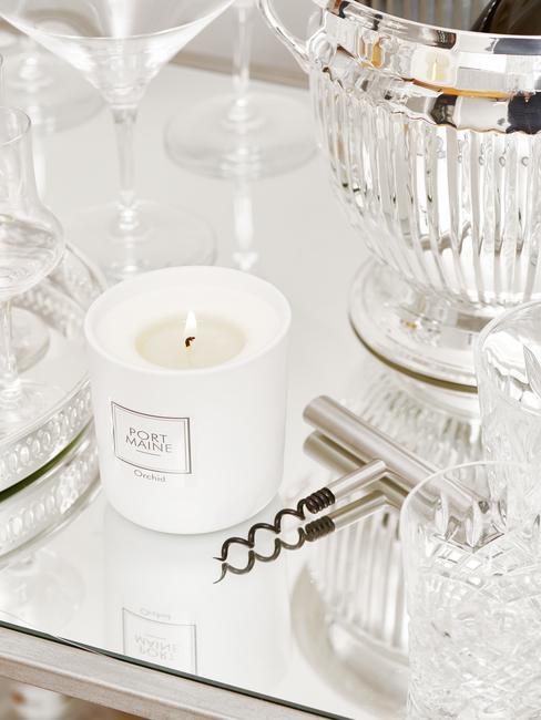 Gedekte tafel met witte geurkaars en zilveren kurkentrekker
