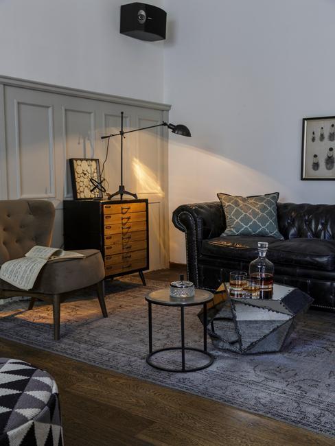 Houtsoorten: donkere meubels in witte woonkamer met zwarte zitbank en metalen bijzettafels naas houten commode