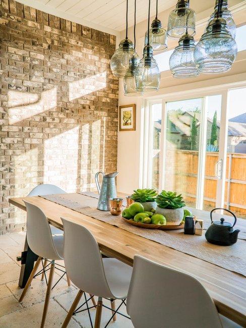 Houten tafel met glazen tafellamp, fruit, moderne stoelen en tegelwand.