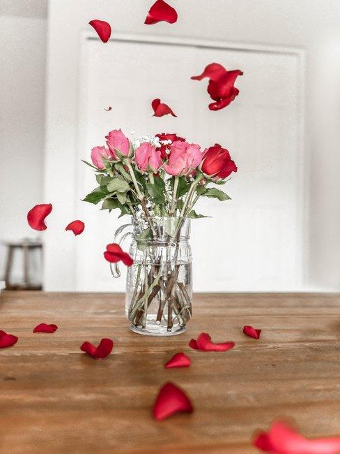 Rode en roze rozen in glazen vaas op houten tafel
