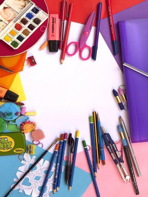 schaar, kwasten, verf en potloden op wit papier