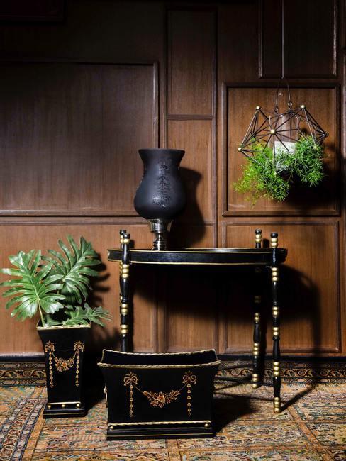 Houten muur met antieke tafel en zwarte vaas