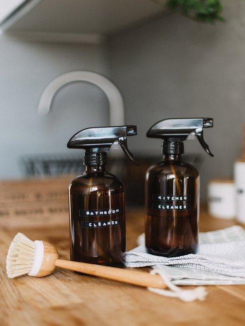 Bruine schoonmaak spuiten met houten afwasborstel op licht houten aanrechtblad