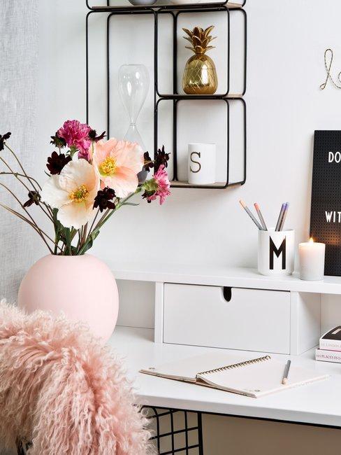 Wit bureau met roze schapenvacht en roze vaas met nepbloemen en zwart wandrek met assecoires