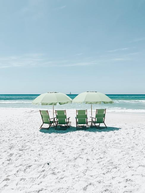 Wit zandstrand met blauwe zee en vier stoelen met twee parasols