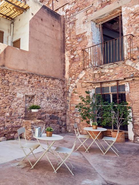 Bakstenen huis met witte klaptafels en stoelen