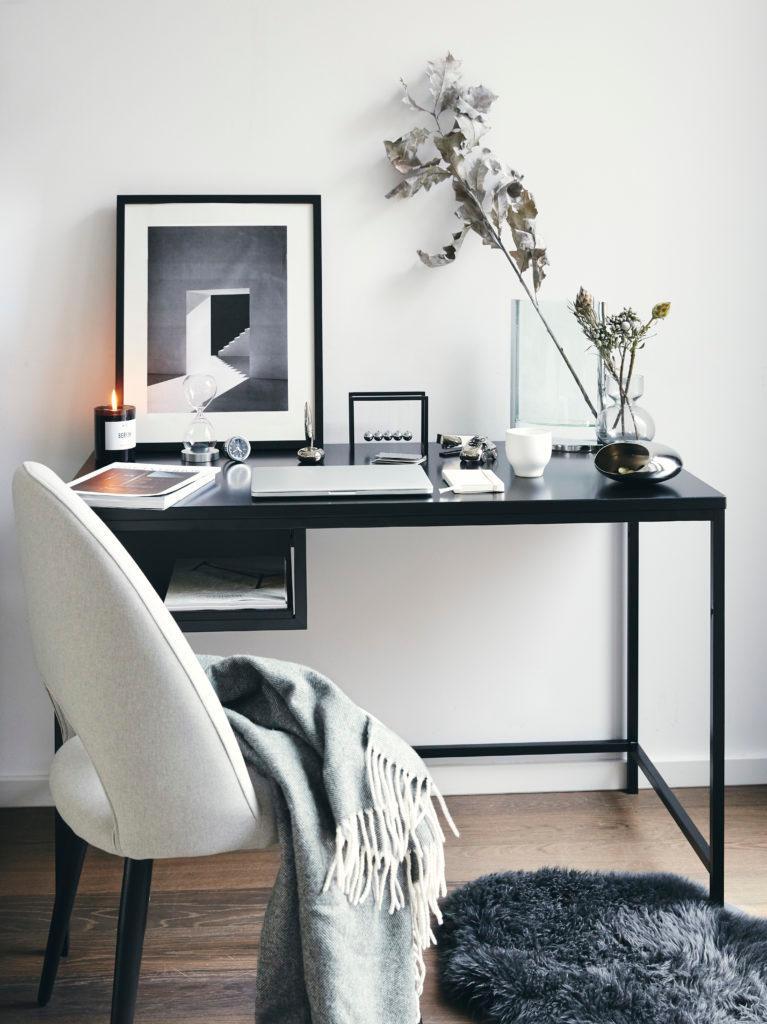 Zwart wit kantoor met schilderij en witte stoel en zwart bureau