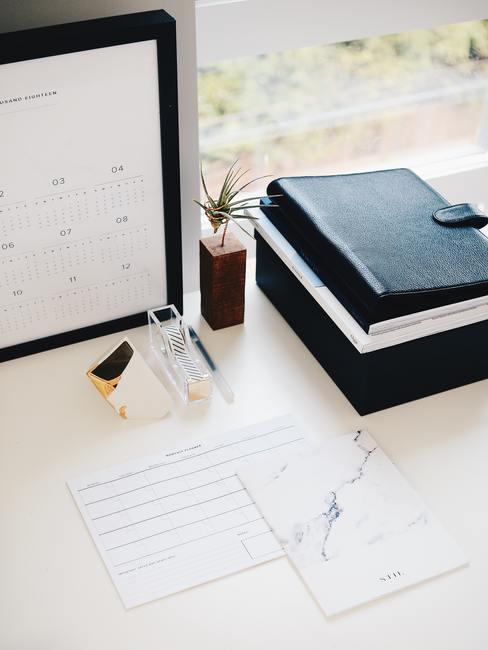 Witte tafel met notitieboeken en kalender in zwart fotolijstje