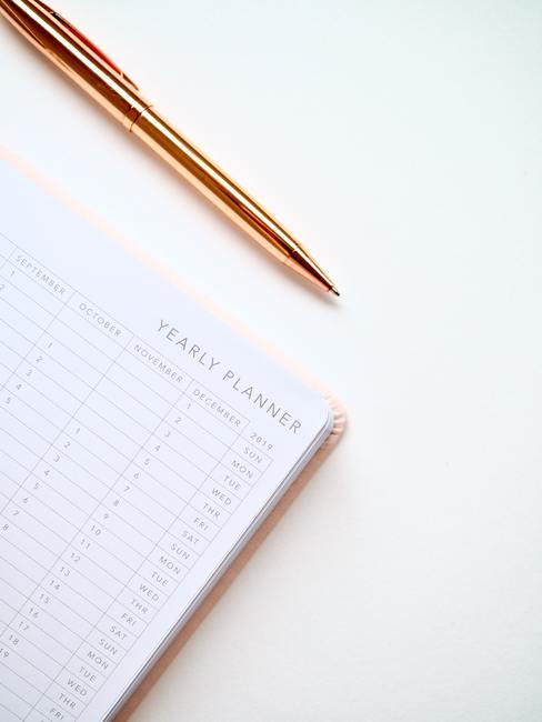 Witte achtergrond met jaarkalender en bronze pen