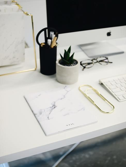 Witte tafel met gouden paperclip macbook en gouden details