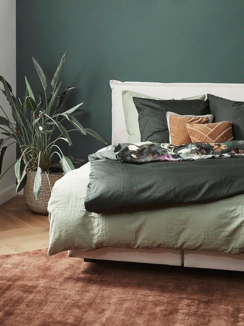 potplanten naast bed met groene lakens en muur