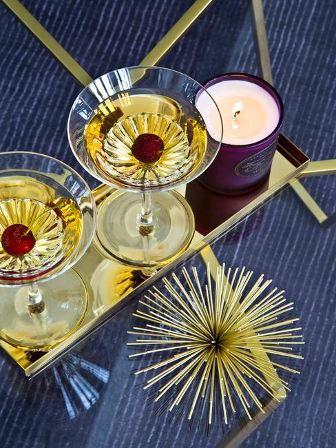Cocktails van boven af gefotografeerd in martini galzen met gouden accessoires
