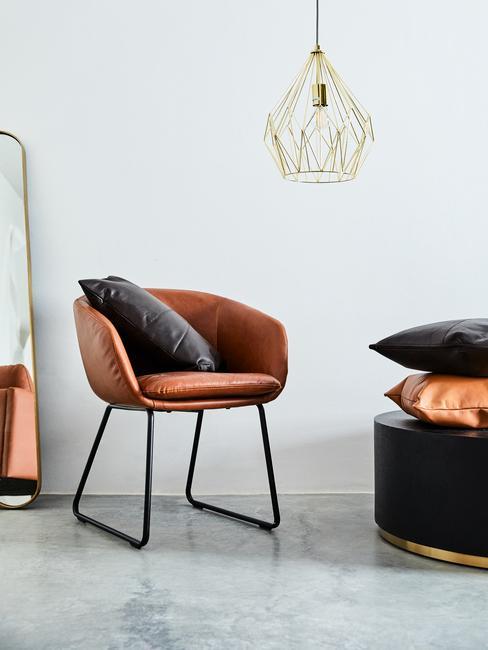 Minimalistische Cognac kleurige stoel met witte wand en grijze betonnen vloer