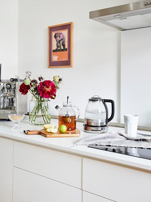 Witte keuken met bloemen in een vaas op een blad en een plank met een pot thee