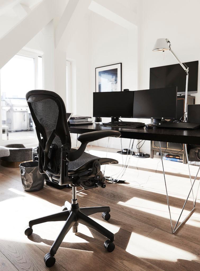 Modern kantoor met een draaistoel en twee schermen op het bureau