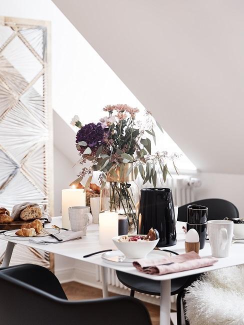 Tafelsetting ontbijt met zwarte stoelen en witte tafel met vaas met bloemen