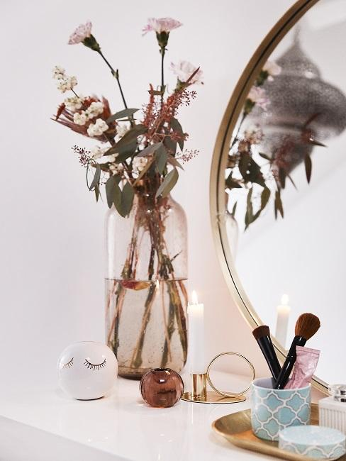 Verjaardagscadeau vrouw bloemen in een glazen vaas met ronde spiegel op witte kast