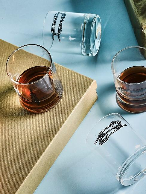 Wisky glazen op gouden cadeau verpakking op blauwe ondergrond