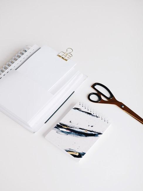 Witte notebook met clip en schaar op een witte tafel voor Save the date kaarten