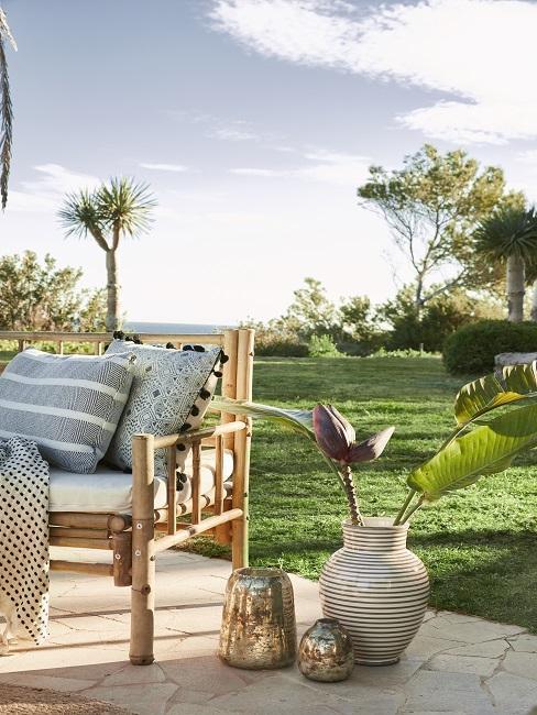 Tuin met bohemian meubels en accessoires op tegels voor grasveld