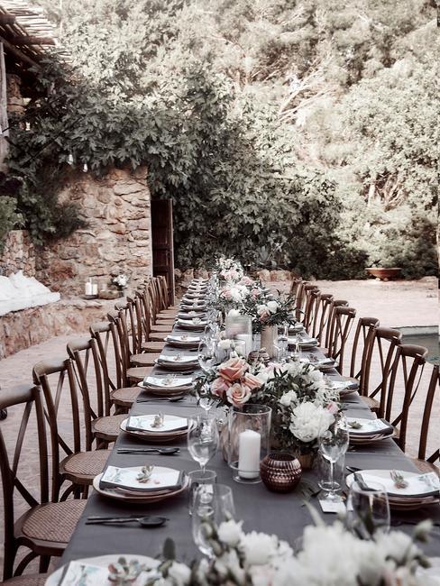Gedekte tafel met serviesset met houten stoelen buiten