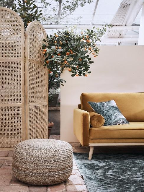 Tuin afscheiding van rotan voor gele velvet bank en rotan poef op vloerkleed
