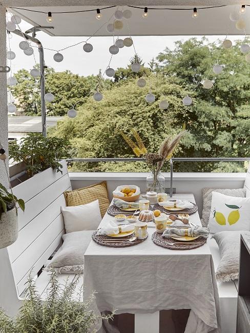 Balkon met witte houten banken en gedekte tafel in moderne stijl