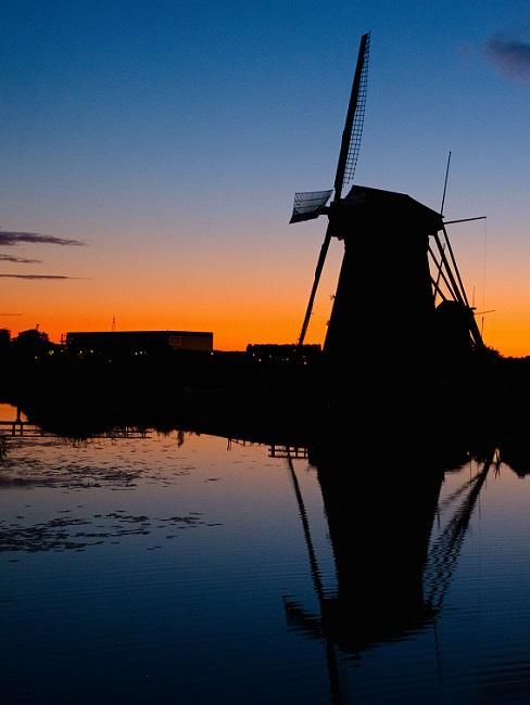 Windmolen met vijver bij zonsondergang
