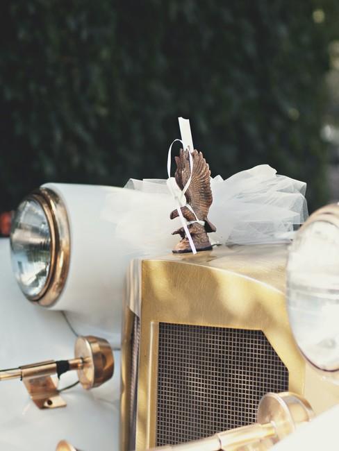 Voorzijde witte auto met trouwaccessoires