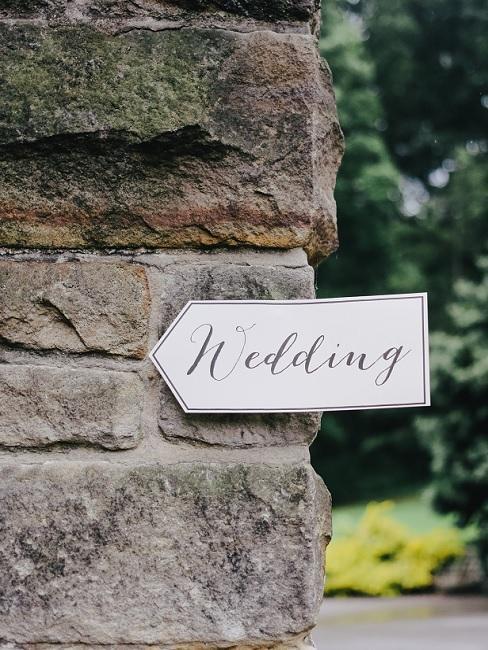 """Decoratief bord met de woorden """"Wedding"""" op een stenen muur"""