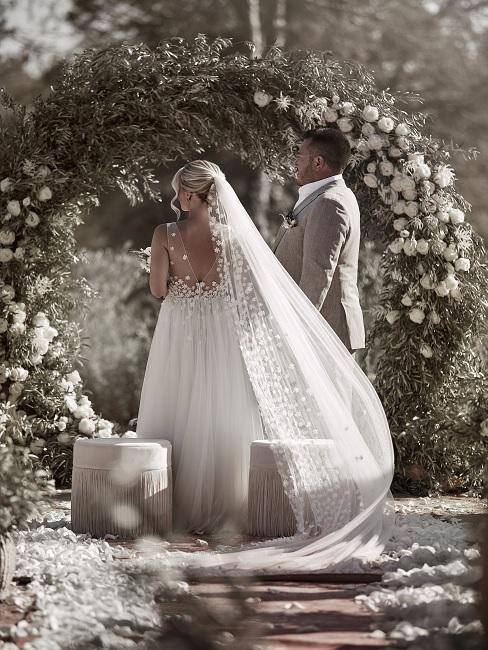 Bruidspaar naast huwelijksdecoratie van bloemen