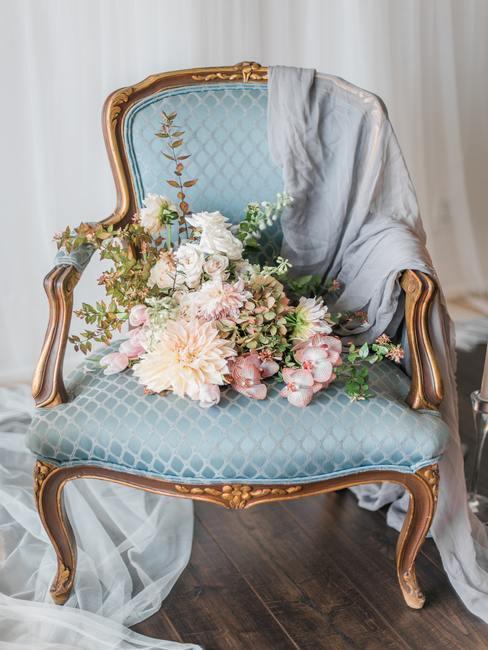 Stijlvolle stoel met een blauwe hoes met een boeket bloemen op de zitting